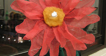 a fabric and wire flower with LEDs at the center sitting indoors on a windowsill at night