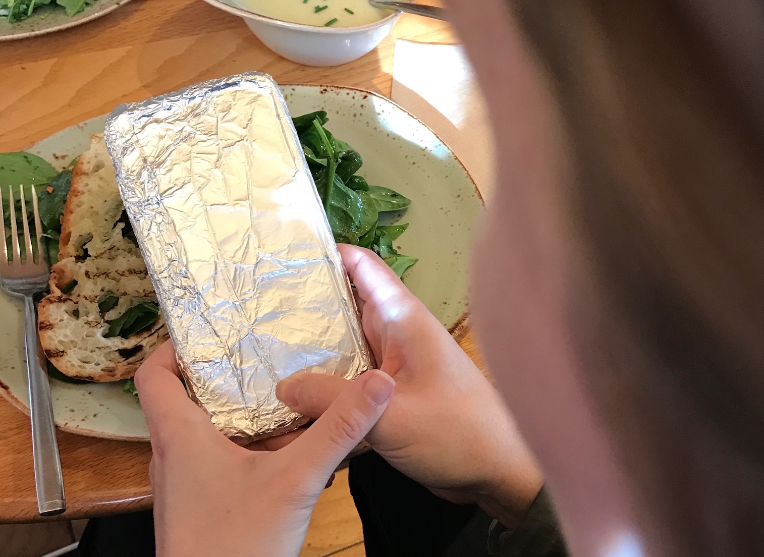 camera being held to take picture of food at a restaurant, but the phone is wrapped in tinfoil