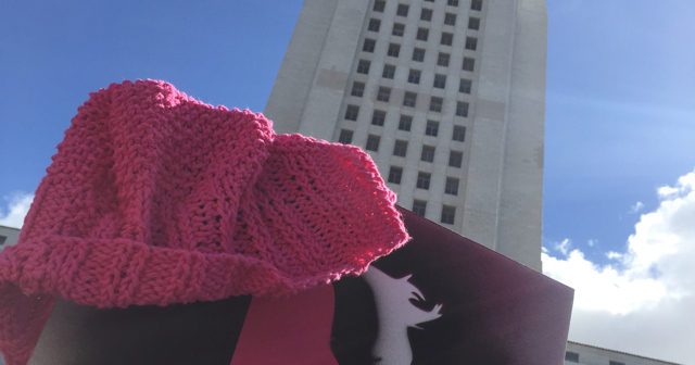 pink knit hat and protest sign with women's march logo held up in front of LA City Hall