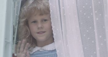 Young girl looks through window with lace curtain and waves