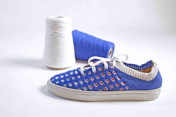 tennis shoe with a blue, white and red knit upper