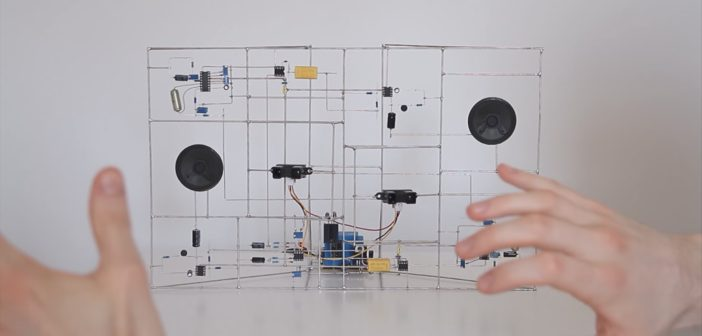 A circuit, but the wires are the structure instead of them being traces on the board. There are two speakers integrated in the structure, and hands in the foreground.
