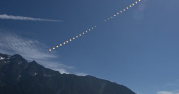 The phases of the sun as it is transited by the moon composited over mountain scenery