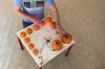 a series of pumpkins of decreasing size arranges around a table with wires leading back to a raspberryPi computer