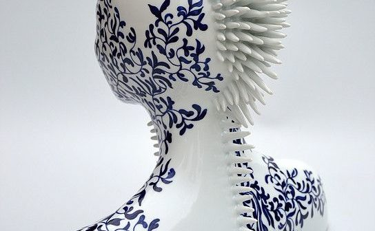 white porcelain bust of a woman with blue floral decorative glaze and a mohawk