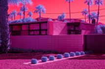 a modernist house in a desert lanscape surrouned by pinks and blues and purples.
