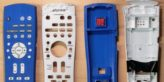 Two sets of a face plate and back plate of a TV remote control. One is white with chew marks, the other is blue and 3D printed.