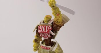 a tangle of noodles in the shape or a warrior wielding a fork overhead in defiance. Armor is made from cup-of-noddles packaging.