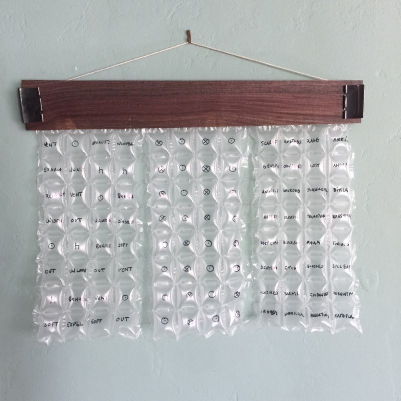 Bubble wrap with words written on each bubble, hanging from a wooden holder secured with binder clips.