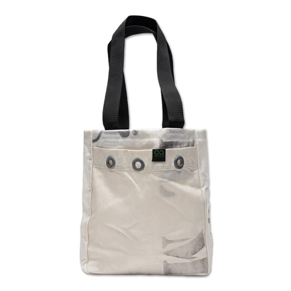 An off-white canvas bag with worn stenciled writing