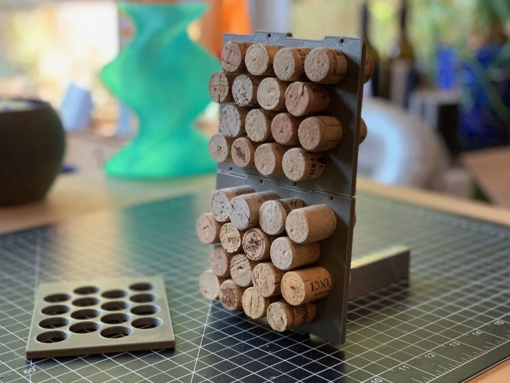 wine corks slotted perpendicularly into a grey plastic panel with cork-sized holes in a compact grid