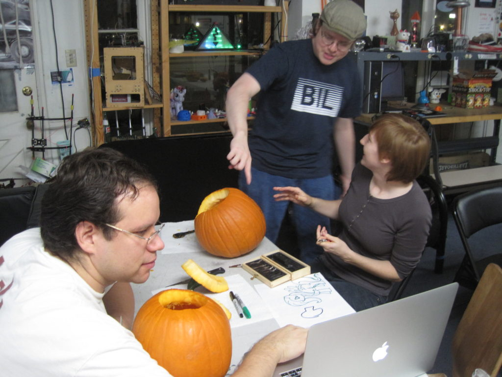 Inside CRASH Space front room, at night time. Justin, in foreground, with pumpkin on table in front of him, consults a laptop computer to his right, while Emily (seated) and Josh (standing) discuss a second pumpkin on the table in front of them.
