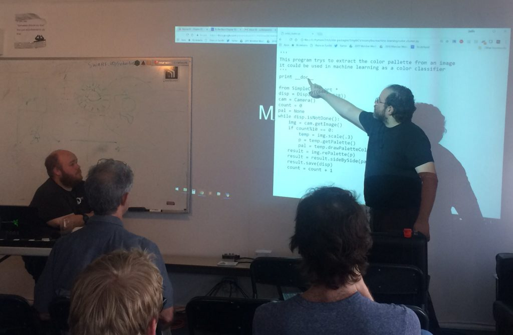 Classroom instruction scene. Justin stands in front of an audience, illuminated by a projector showing computer code. Justin points at the projector image. Kyle, seated to the left, and audience members are seen in the foreground, looking on while Justin instructs