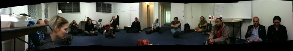 Wide panorama picture of the front room of CRASH Space at night, with people sitting on floor because there is no furniture