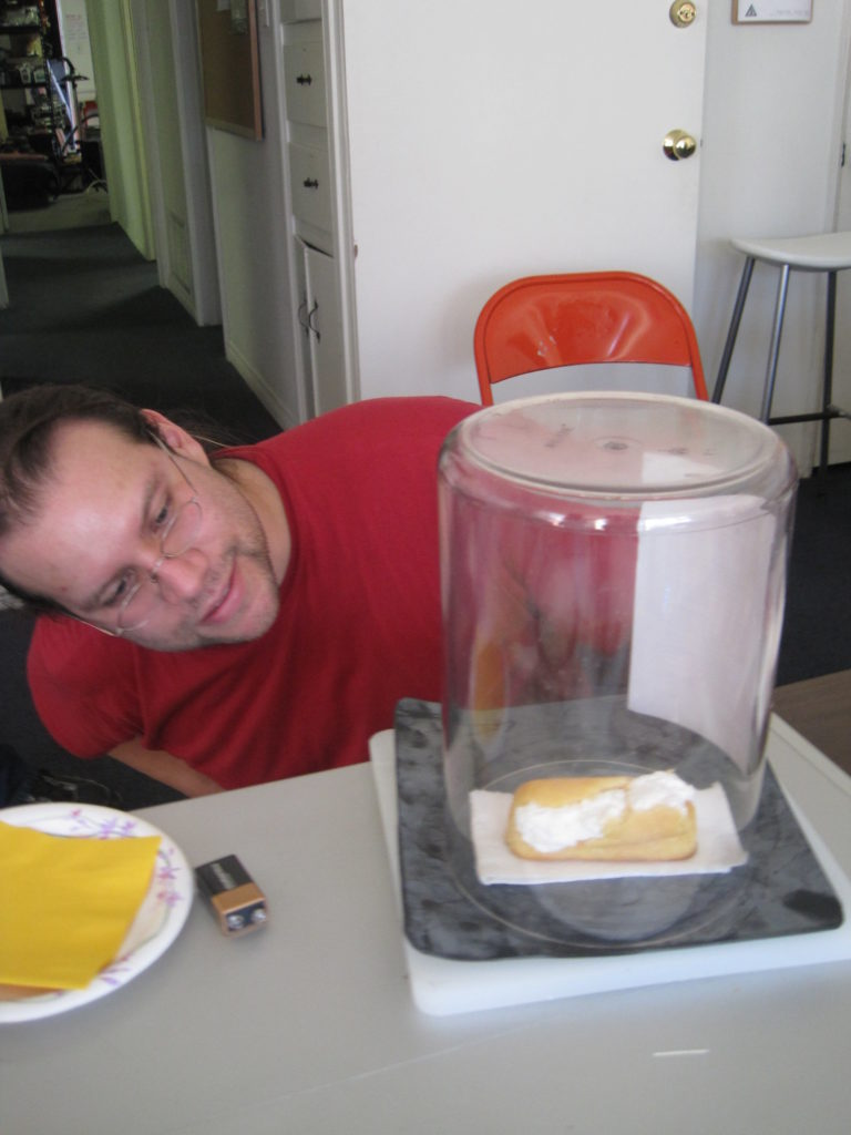 Justin, seated in the front room of CRASH Space in the daytime, looks at a bell jar on the table in front of him, which contains a Twinkie that has expanded after being exposed to a vacuum