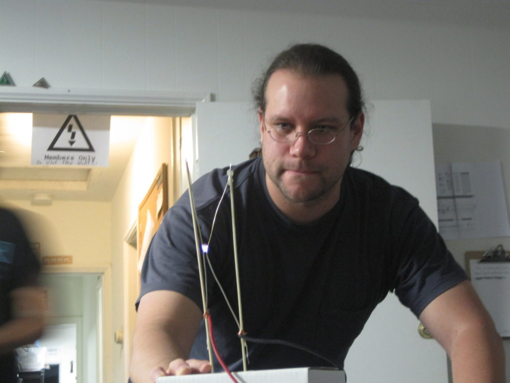 Justin, standing in the CRASH Space front room during the daytime, hands resting on the table, looks at a Jacob's Ladder on the table in front of him with an electrical arc between its rods.