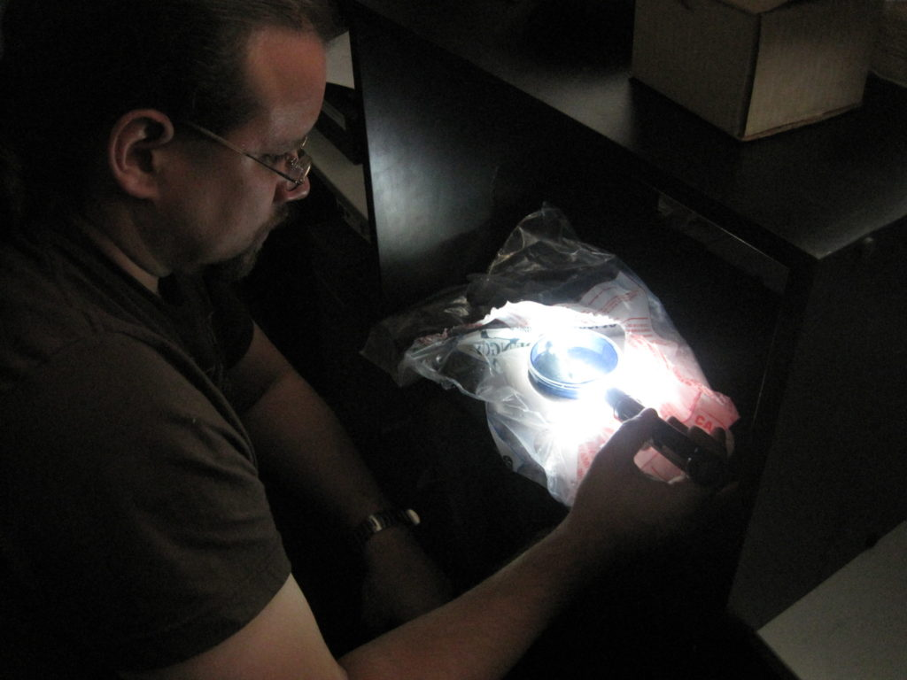 In a darkened room, Justin shines a flashlight on a circular object on the desk in front of him