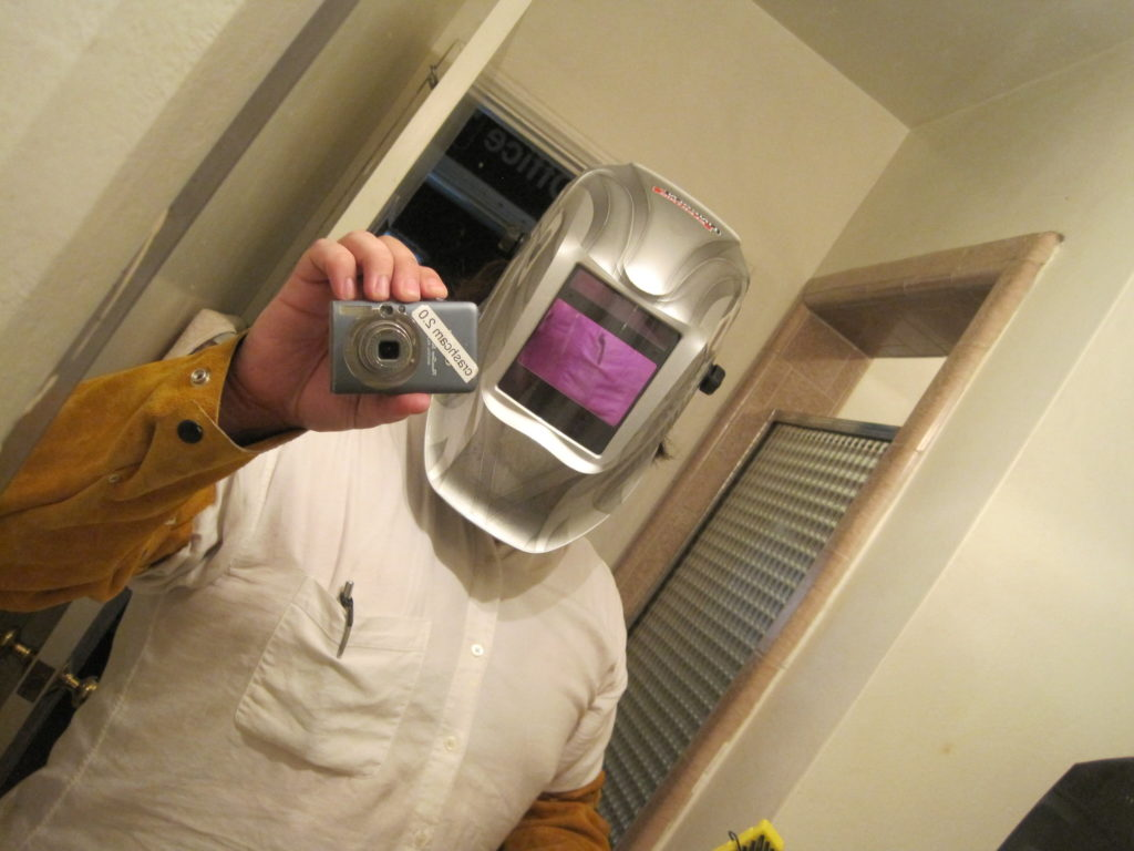 Self portrait in a bathroom mirror at CRASH Space. Justin is wearing protective gear for welding, including a darkened face visor. He holds the camera up to take the picture
