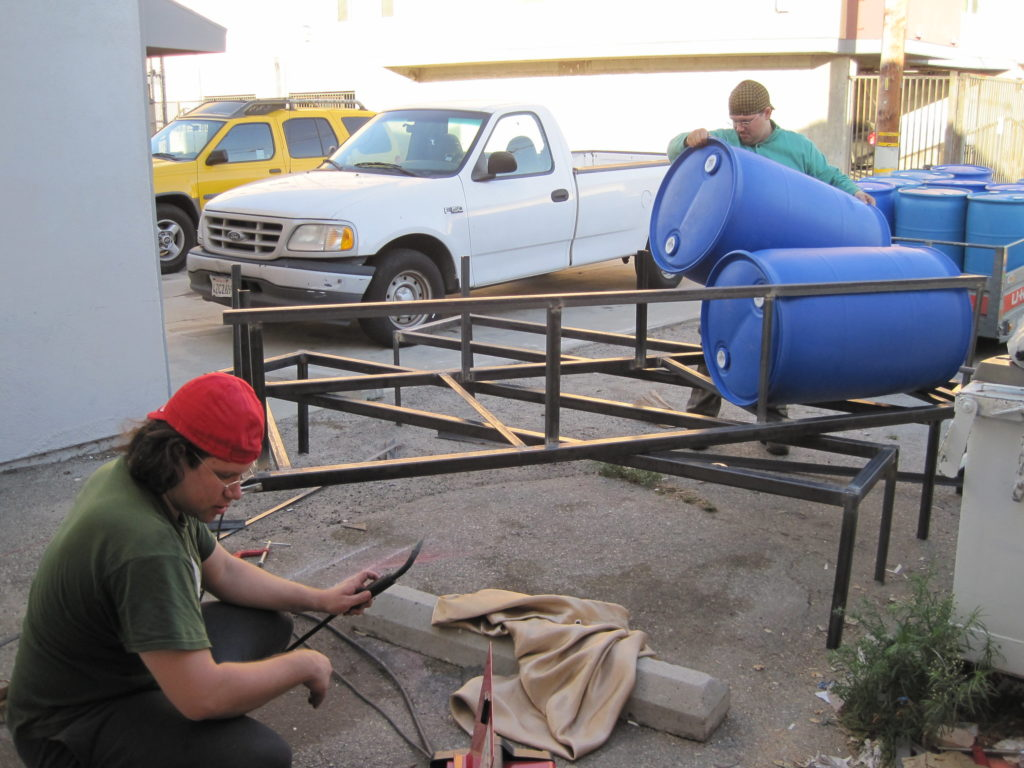 Wide picture of the parking lot behind CRASH Space, where Justin and Naim work on welding a steel frame and loading it with 80 gallon drums to make a boat for Ephemerisle. Justin crouches in the foreground, operating the welder. Naim stands in the background loading a blue plastic 80 gallon drum onto the frame they have been building