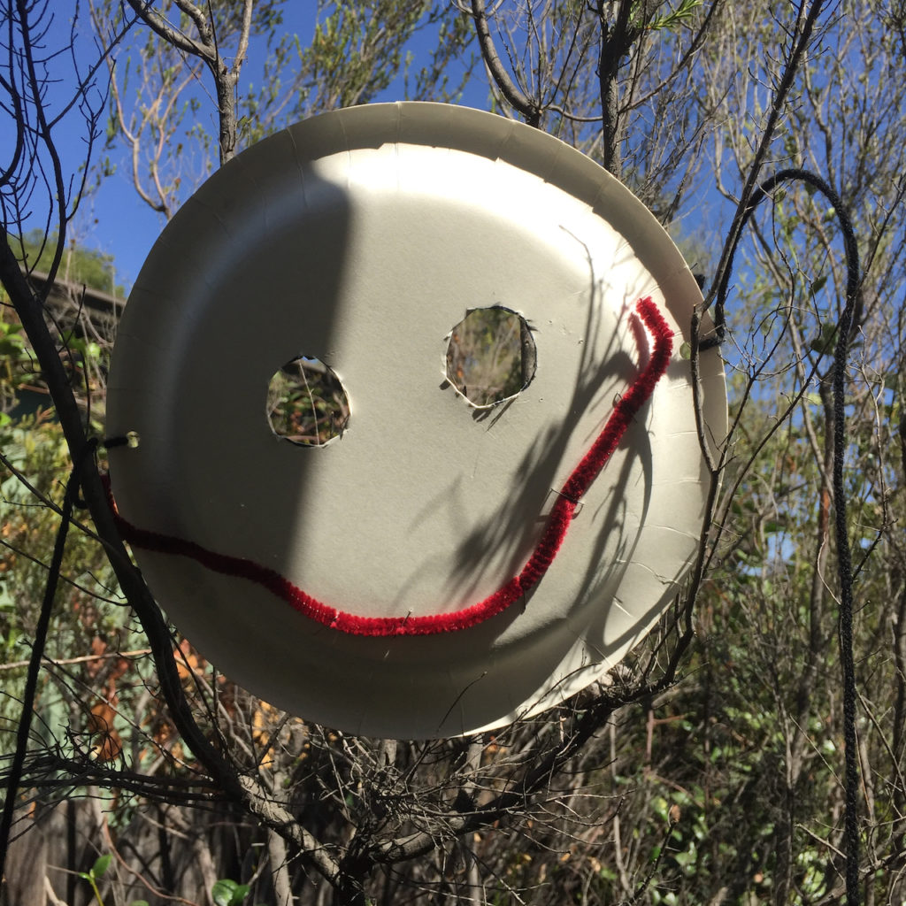 A mask made from a paper plate hung in a tree. The eyes are sloppily cut out and the mouth is maroon pipe cleaner stapled haphazardly in place.